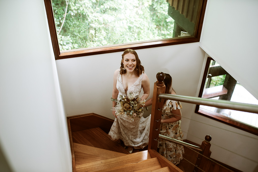 Bride Sarah walking up the stairs of the Cairns Treehouse going to her Wedding Ceremony at the top of the stairs.