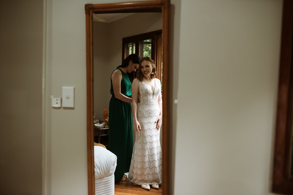 Bride Sarah pictured in front of a mirror getting her dress on. She is being assisted by friend Kate moments before getting married to her sweetheart in Cairns