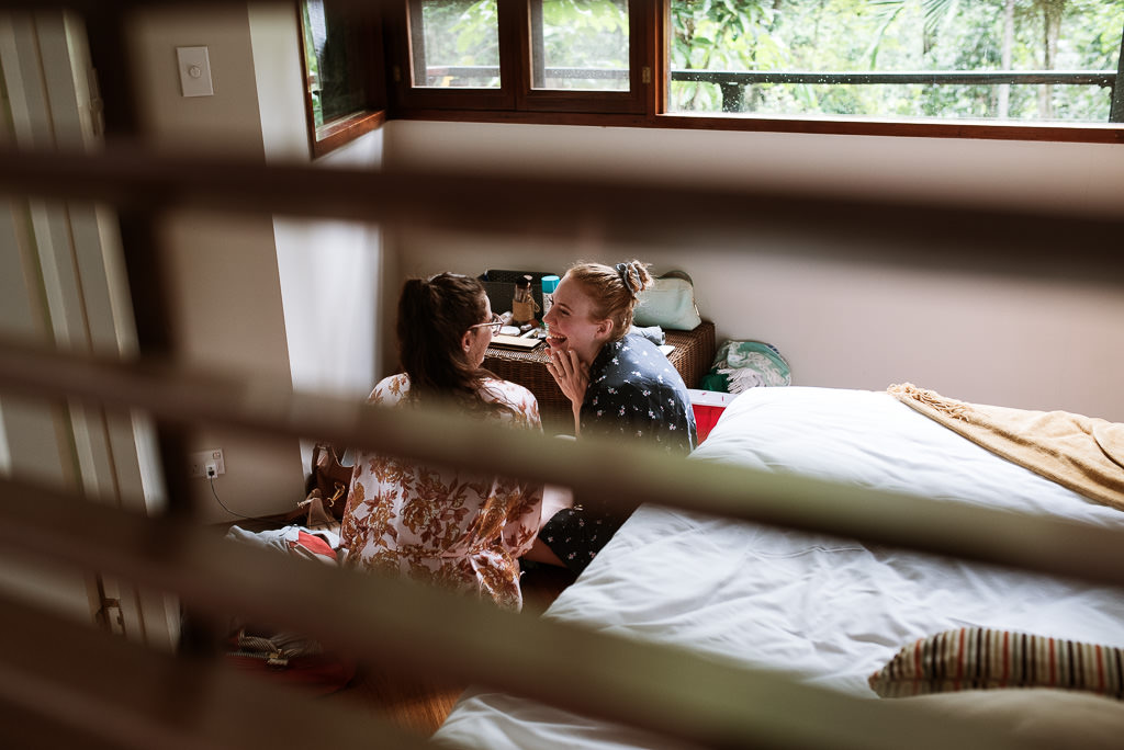 Bride Sarah sharing a pre wedding moment with friend Kate before she prepares for her wedding day. Photographed through a window peeking in at her joy and excitement.