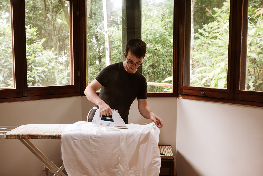 Groom Brendan Ironing his shirt in preparation for his wedding ceremony. Cairns Treehouse Wedding Terri Hanlon Photography