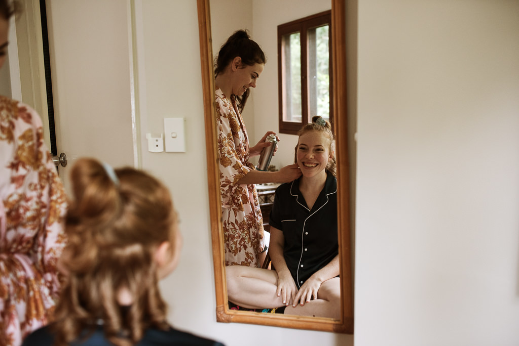 Bride Sarah having her hair done by friend Kate on her wedding day in her Cairns Treehouse