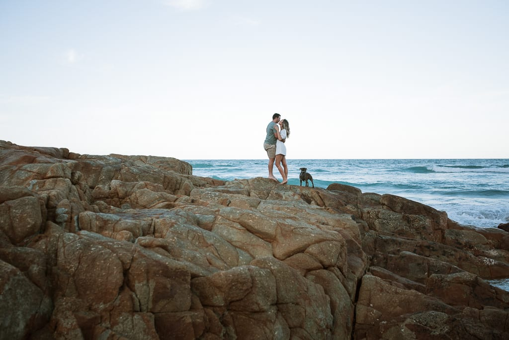 Couple hugging on the rocks at First Bay Coolum