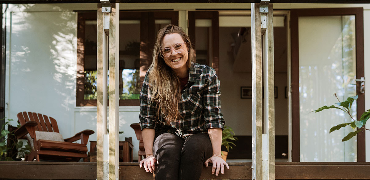 Terri Hanlon Photographer sitting on the deck of a tiny house in Maleny