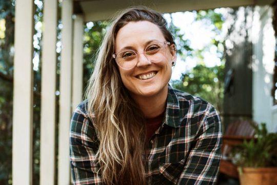 Terri Hanlon Photographer sitting on the deck of a tiny house